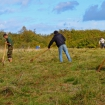 Volunteers raking wildflower meadow