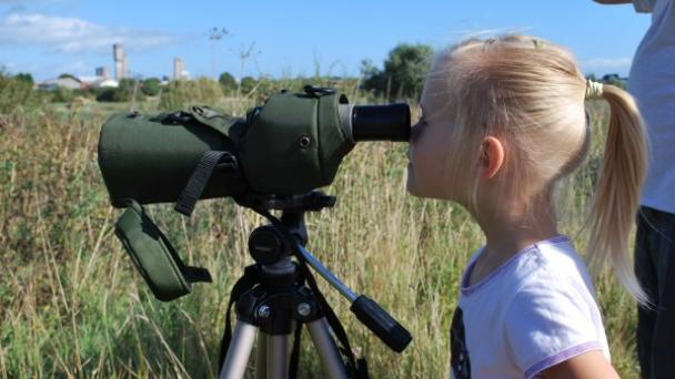 Young girl with blonde hair looks into a bird-watchers telescope while out with her school on Portrack Marsh
