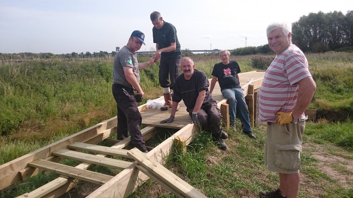 Group of male volunteers constructing a viewing platform.
