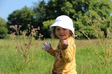 Young girl looking for mini-beasts amongst open grassland and wildflowers
